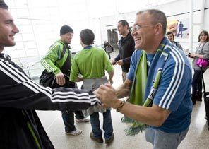 Seattle Sounders FC returns to Seattle with a Major League Soccer playoff berth after defeating the Kansas City Wizards Saturday night. Chuck Amon, right, from Federal Way, came to Seattle Tacoma International Airport to welcome the team home including midfielder Stephen King, left.