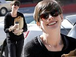 Anne Hathaway dresses down in a tracksuit as she giggles to herself while grabbing an early morning coffee