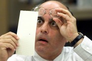 Broward County Canvassing Board member Judge Robert Rosenberg stares at a dimpled punchcard ballot November 23, 2000 during the recount of the 2000 presidential election.