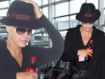 Jenny McCarthy slips through the crowds all in black as she leaves a New York airport with her son Evan