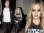 Going goth: Avril Lavigne sports heavy panda eyes and lace up leather trousers for a date with fiancé Chad Kroger