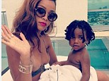 Oh baby! Rihanna cuddled up to a toddler poolside on Sunday afternoonchild: A