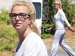 A bespectacled Britney Spears wears skintight tracksuit pants that hug every curve as she leaves rehearsal studio