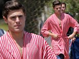 Brace yourself ladies! Zac Efron reveals his super toned chest as he walks around on the set of his new movie in a striped robe