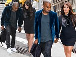 Her hero! Kanye West steers Kim Kardashian over a drain as she steps out in another little black dress with killer heels
