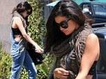 Side splitting action: Selena Gomez shows off black lacy bra as she heads to work in denim dungarees