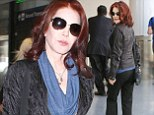 Turning back the hands of time: Priscilla Presley showcases her youthful good looks as she struts through LAX in low-key leather