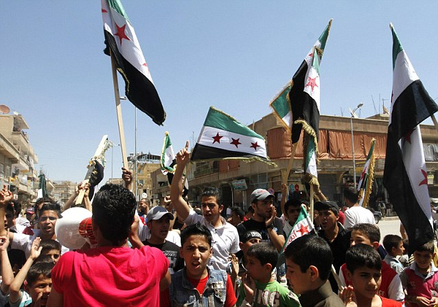 Protestors: Demonstrators chant slogans and wave Syrian opposition flags as a boy shouts into a loud hailer during a protest against Syrian President Bashar al-Assad afer Friday prayers