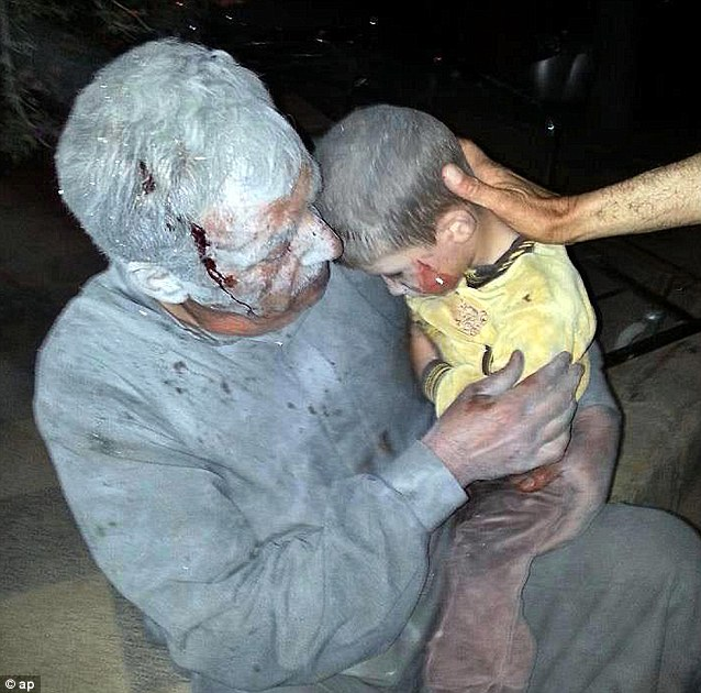 Battle wounds: A wounded Syrian man holding his injured son after an air raid in the northwestern of Syria. The White House has said the Syrian government has twice used chemical weapons