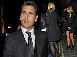 Partying like a lord: Scott Disick stumbles out of London club with two blondes while Kourtney and his children head to Greece