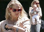 Doting mother Elizabeth Berkley clutches her cherubic son Sky as the pair step out for baby class