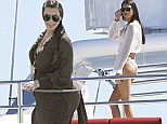All aboard! Kim Kardashian covers her baby bump in black maxi dress as sister Kendall bares her body in bikini on Mykonos holiday