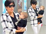 Glamorous granny! Kris Jenner cuts a striking figure in checked jacket and white jeans as she carries baby Penelope through Greek airport