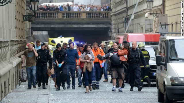 Police officers, paramedics and firefighters lead injured people away from the scene of a powerful gas explosion at a building in the historic center of Prague, Czech Republic, on Monday, April 29. The blast injured at least 35 people.