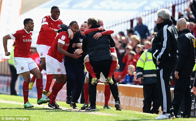 Roaring success: Barnsley players mob Chris O'Grady (right) after his priceless second sealed the three points
