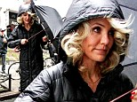 Don't rain on my parade! Cameron Diaz tries to keep her big curls dry in New York downpour