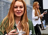 Lindsay Lohan puffs on a cigarette as she picks up her Porsche after getting car towed for 'illegal parking'