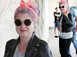 Clashing must be declared at customs: Kelly Osbourne's hot pink headscarf makes her purple head look stranger