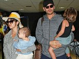 Happy family: Kourtney Kardashian and Scott Disick dotingly carry their little ones through Los Angeles airport on Wednesday after jetting in from Greece
