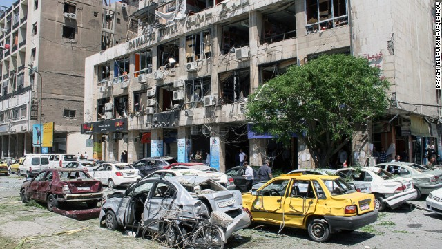 People walk past a damaged building and multiple destroyed cars at the site of an explosion in Damascus where at least 13 were killed on April 30.