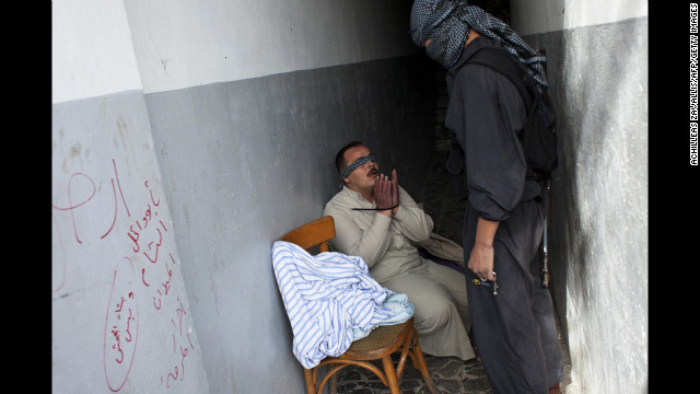 A Syrian rebel interrogates a handcuffed and blindfolded man suspected of being a pro-regime militiaman in Aleppo on October 26.