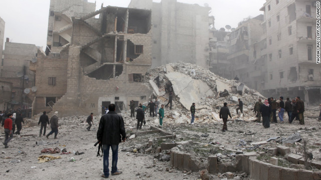 People stand in the dust of a building destroyed in an airstrike in Aleppo, Syria on February 3.