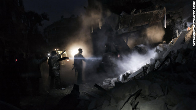 Syrians look for survivors amid the rubble of a building targeted by a missile in Aleppo on January 7.