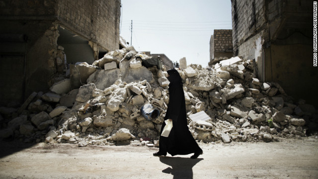 A woman walks past a destroyed building in Aleppo on September 13.