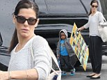 Budding artist: Sandra Bullock picked up her son Louis from school toting a large photographic art collage in Los Angeles, on Tuesday