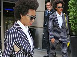 Solange Knowles' fashion adventure takes a wrong turn as she wears a bizarre pinstripe suit that's slashed open to reveal her bra