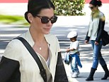 Easy rider! Sandra Bullock sweetly cradles son Louis while clad in a leather jacket and motorcycle boots
