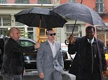 Rain, rain, go away: Evidently not content with his Bronx-born lady's shelter, Casper ensured the rain was kept at bay by insisting not one, but two, assistants held umbrellas over his head to guide him to cover