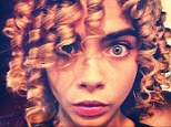 'Corkscrew me': Cara Delvingne posted a picture of herself with her hair in tight ringlets on Thursday, as she geared up for a shoot in Malaysia