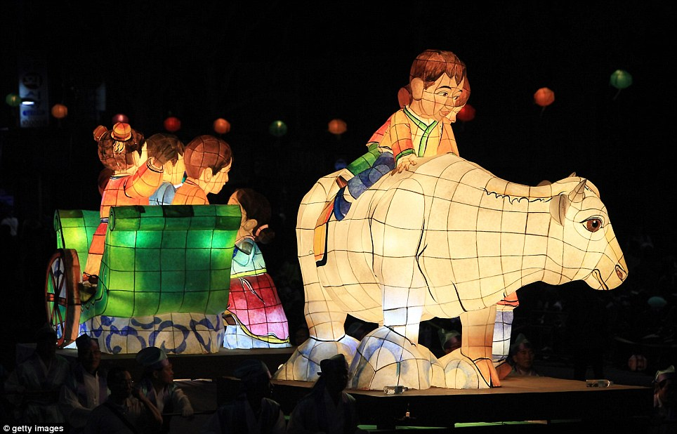 A lantern depicting a boy riding a cow is carried down a Seoul street as part of the Buddha birthday celebrations