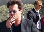 Stressed Johnny? Depp puffs on a cigarette onset of new flick while costar Paul Bettany looks ready for business in a suit