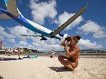 Ultimate plane spotting: A tourist takes pictures on Maho beach in St Maarten as a passenger jet flies overhead towards the landing strip at Princess Juliana International Airport