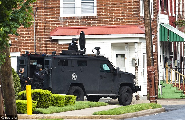 Armed: SWAT police personnel stand guard outside the South Trenton home where a man held several children hostage, having killed their mother