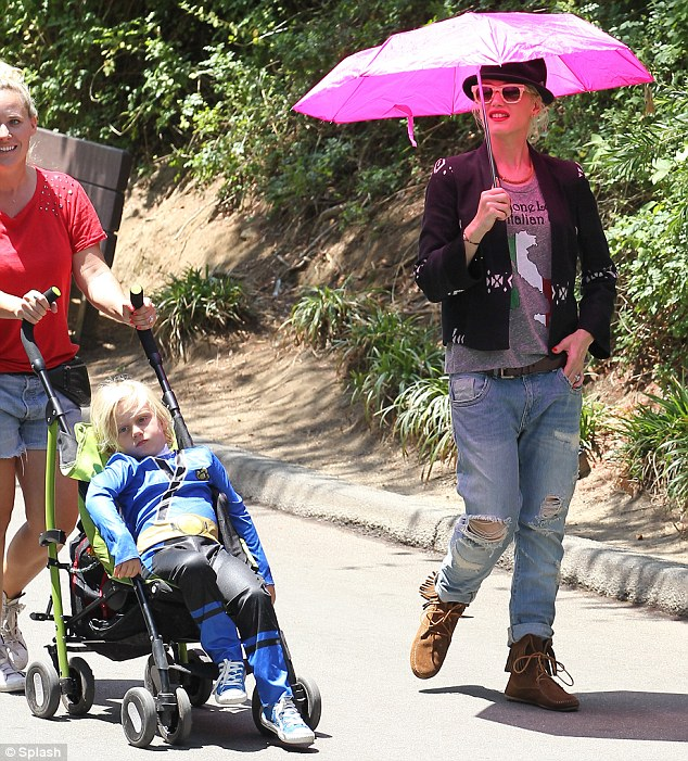 Brolly good idea: Canny Gwen made sure she brought a lackey to push the stroller while she shielded herself from the sun