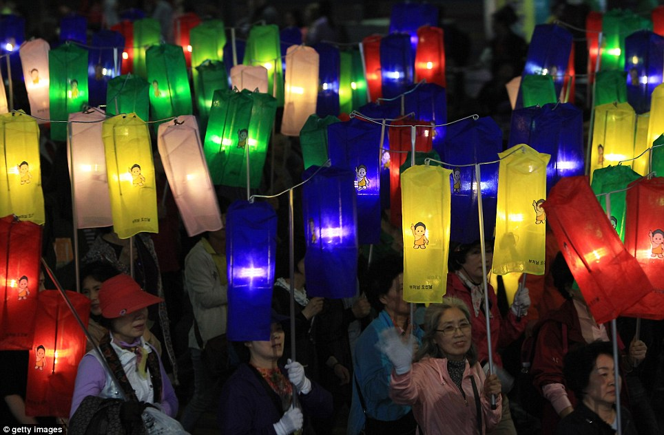 Procession: South Korean Buddhists carry coloured lanterns as they make their way down a Seoul Street to celebrate Buddha's birthday