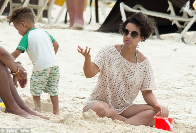 Playing around: Alicia and her son make sandcastles on the beach, just yards from their luxury hotel