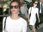 Emma Watson highlights her every curve in a figure-hugging white dress as she touches down for Cannes