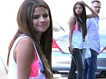Flirty in fluro! Selena Gomez flashes her hot pink bra as she wears a white vest top to the studio