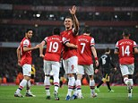 Heading for fourth: Lukas Podolski celebrates after scoring against Wigan