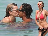 Sealed with a kiss! Rita Rusic slips into a coral two-piece to smooch toyboy lover as they frolic in the Miami sea