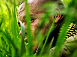 SAW gunner takes a break in high grass during a cordon and search