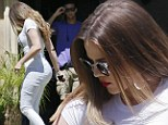 Bum's the word! Khloe Kardashian dons skintight white skinny jeans after posting an Instagram picture of bare-bottomed girls for fit-spiration