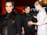 Sheer baby bliss! Kim Kardashian invites a belly rub from Amanda DeCadenet as she displays her growing belly and black bra in a transparent top