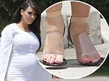 Suffering for style! Heavily pregnant Kim Kardashian's swollen feet are severely pinched as she squeezes them into sky-high perspex stilettos