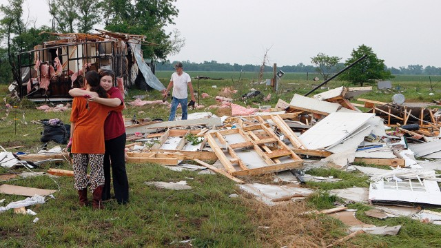 Shawnee, Oklahoma, residents embrace on May 20 as they search through the remains of their home, destroyed by a tornado on May 19.