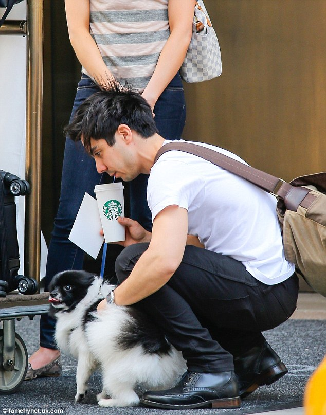 Helping hand: Ben assisted his new wife with the pup, as he held a Starbucks cup in his other hand